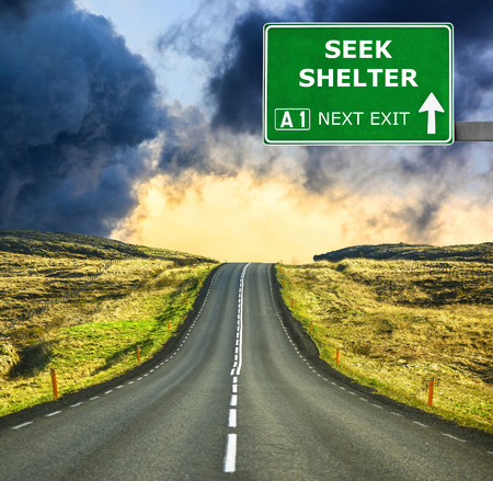 SEEK SHELTER road sign against clear blue sky Stock Photo