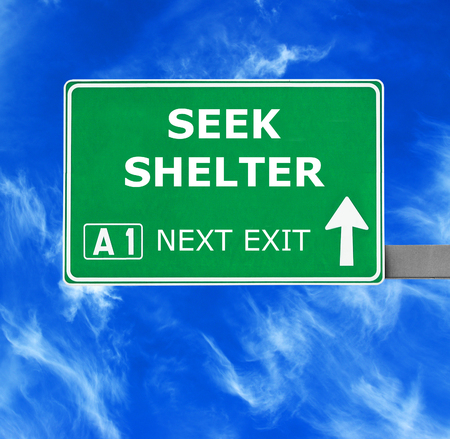 take down notice: SEEK SHELTER road sign against clear blue sky Stock Photo