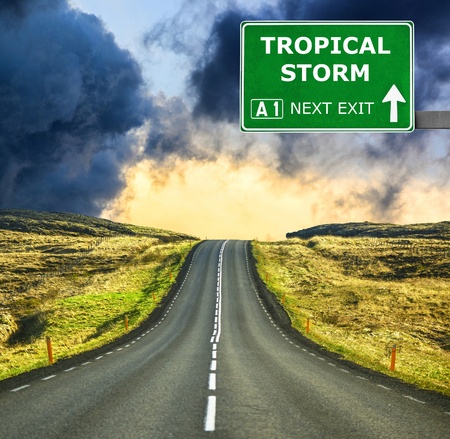 deluge: TROPICAL STORM road sign against clear blue sky Stock Photo