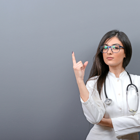 advertising woman: Young beautiful female doctor showing blank area Stock Photo
