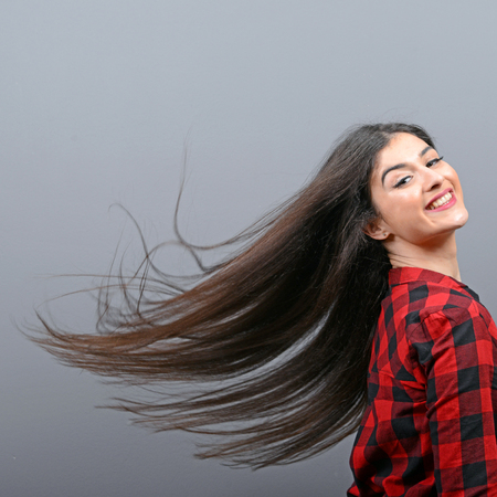 flicking: Young woman flicking her hair and posing against gray background Stock Photo