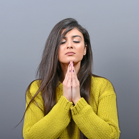 greyish: Woman praying about something or begging for mercy against gray background