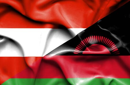 malawian flag: Waving flag of Malawi and Austria Stock Photo