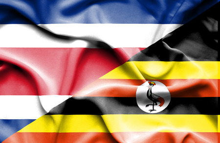 costa rica: Waving flag of Uganda and Costa Rica Stock Photo