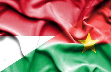 monaco: Waving flag of Burkina Faso and Monaco Stock Photo