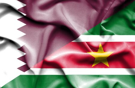 suriname: Waving flag of Suriname and Qatar Stock Photo