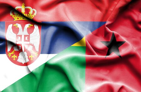 guinea bissau: Waving flag of Guinea Bissau and Serbia Stock Photo