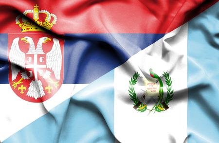 serbia: Waving flag of Guatemala and Serbia Stock Photo