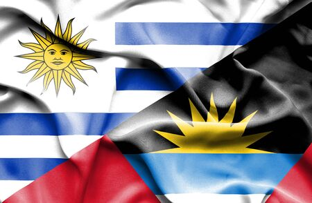 antigua: Waving flag of Antigua and Barbuda and Uruguay Stock Photo