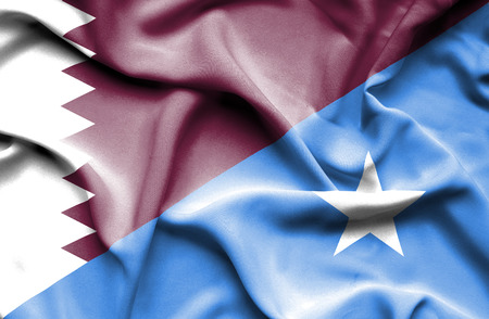 somalian culture: Waving flag of Somalia and Qatar Stock Photo