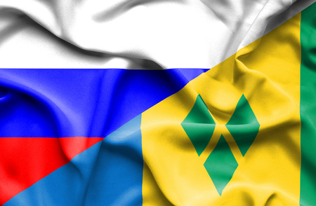 grenadines: Waving flag of Saint Vincent and Grenadines and Russia Stock Photo