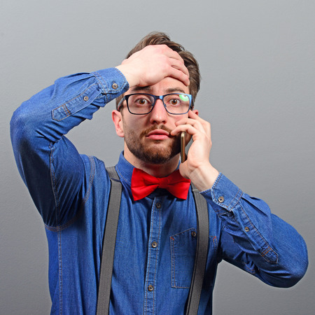 forgetful: Portrait of forgetful or shocked man talking on cellphone against gray background
