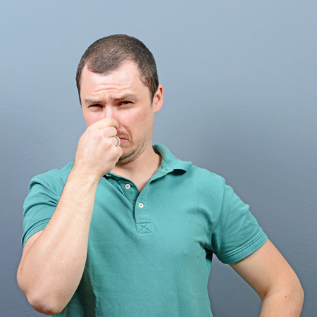 stinks: rtrait of man covering nose with hand showing that something stinks against gray background Stock Photo