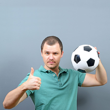 supporter: Portrait of man holding football with thumb up - Football fan supporter or player concept