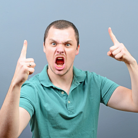 outraged: Portrait of a angry threatening man screaming against gray background