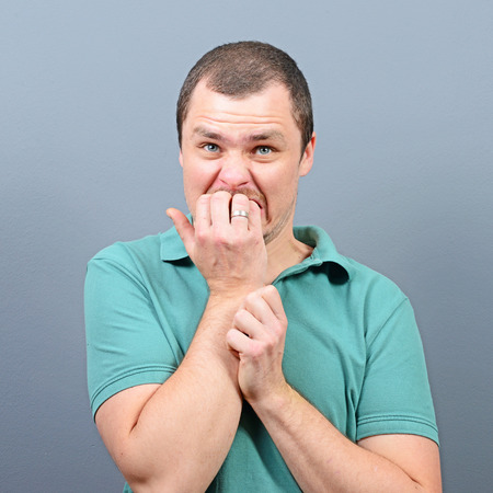Portrait of a man biting nails and being scared against gray background Stock Photo