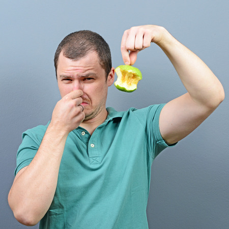 intolerable: Portrait of man covering nose with hand showing rotten apple against gray background Stock Photo