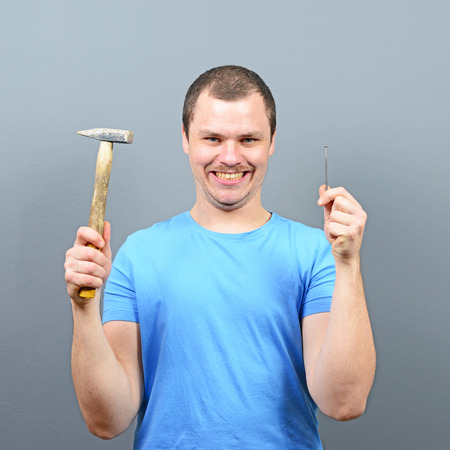 settler: Portrait of funny man holding hammer and nail