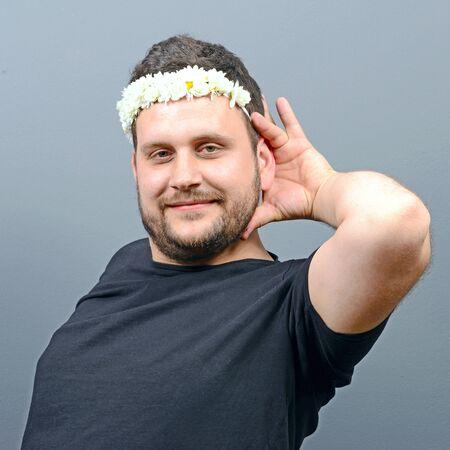 ladylike: Portrait of funny chubby man wearing flower wreath on head and behaving feminine against gray background