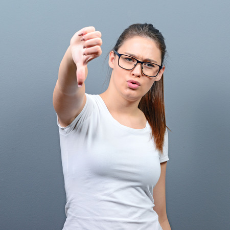disapproval: Portrait of a woman showing thumb down as disapproval against gray background