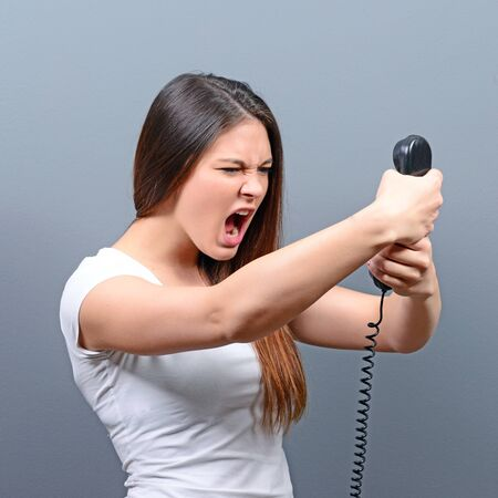 unpleasant: Portrait of woman having unpleasant phone calll against gray background Stock Photo