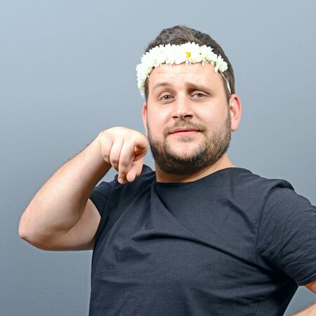 behaving: Portrait of funny chubby man wearing flower wreath on head and behaving feminine against gray background