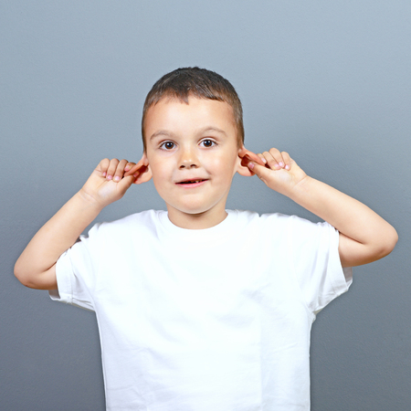 prankster: Cute little boy kid making funny face and pulling ears against gray background