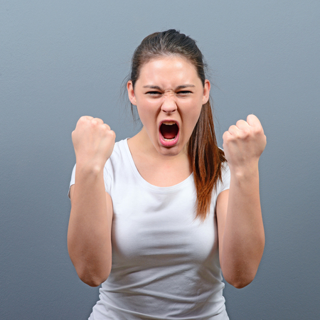 Portrait of happy woman exults pumping fists ecstatic celebrates success against gray background