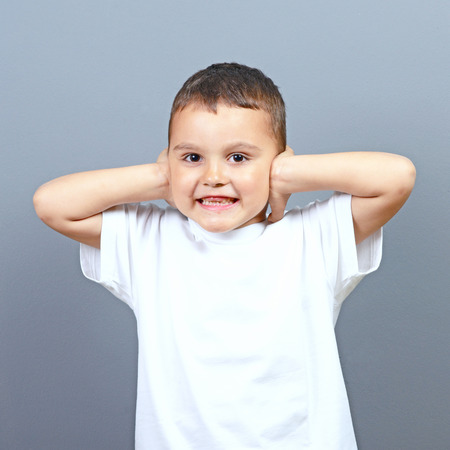 hands covering ears: Cute little boy kid covering his ears with hands against gray background