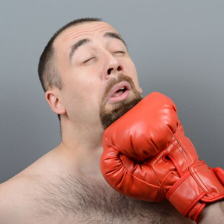 looser: Portrait of funny fat boxer getting punch in face against gray background