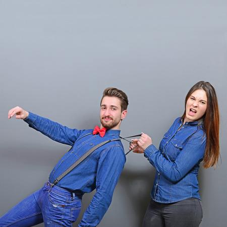 working woman: Woman pulling mans suspenders - Doenst let him go ir run away
