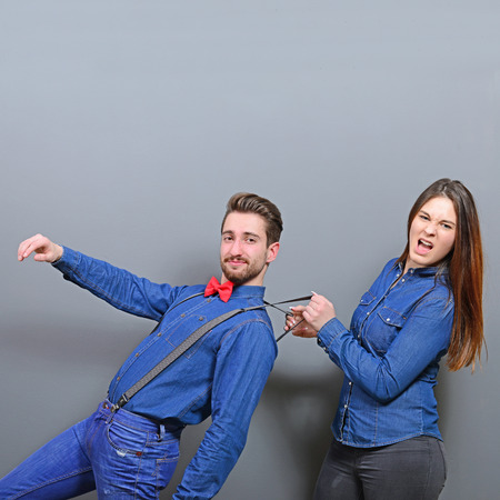 bound woman: Woman pulling mans suspenders - Doenst let him go ir run away