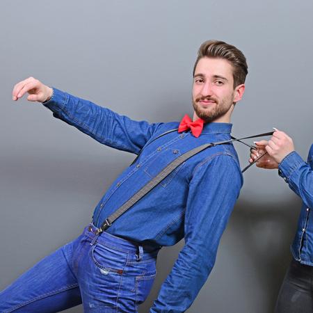let go: Woman pulling mans suspenders - Doenst let him go ir run away
