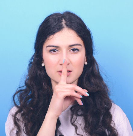 shushing: Portrait of girl with gesture for silence against blue background