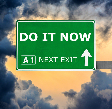 without delay: DO IT NOW road sign against clear blue sky