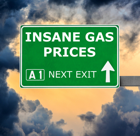 gas prices: INSANE GAS PRICES road sign against clear blue sky