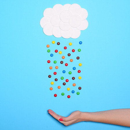 Multicolored sweets raining from cotton clouds in hand against blue background - Flat lay