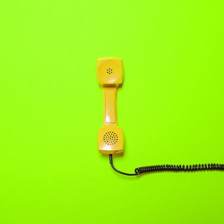Retro teléfono tubo de color amarillo sobre fondo verde fluorescente - Diseño mínimo Foto de archivo