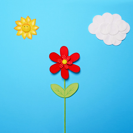 fairy  tail: Fairy tail scene made of various objects on blue paper - Childrens story background - Cotton clouds and sun with red wooden flower against blue paper - Flat lay