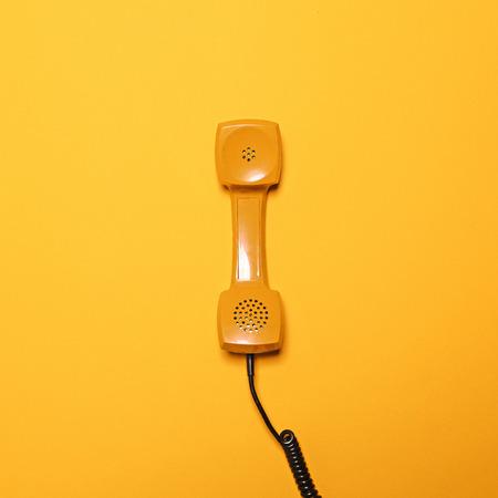 레트로 노란색 전화 튜브 노란색 배경 - 평면 누워