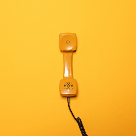 Retro gele telefoon buis op gele achtergrond - plat lag