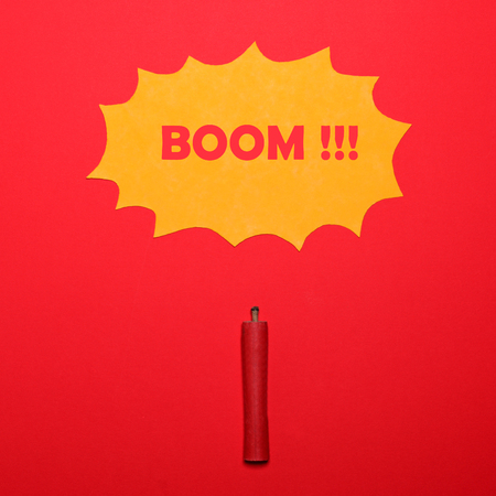 aerial bomb: Dynamite stick with BOOM sign above on red background - Explosion concept - Minimal design
