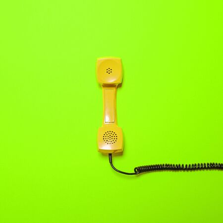 phone cord: Retro yellow telephone tube on fluorescent green background - Minimal design