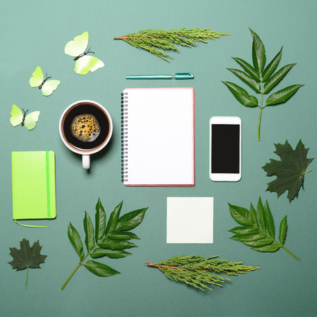 botany: Cup of coffee with green leaves butterfly book pen and cell phone on green background - Flat lay Stock Photo