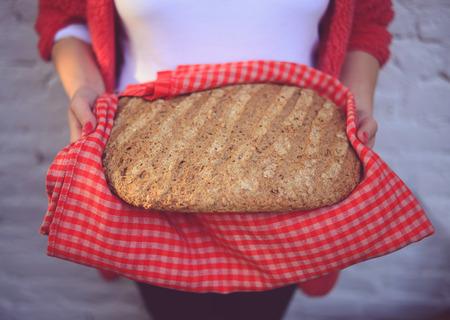 meade: Woman baker holding freshly baked bread - Home meade bun of bread Stock Photo