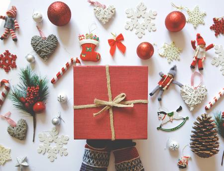 Vlak leg van Kerstmisdecoratie en ornamenten op witte backgroundand vrouwenhand die rode giftdoos houden - Trendy minimaal vlak ontwerp