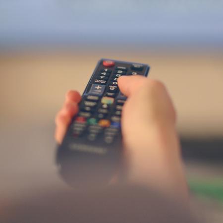 Mano che regge il telecomando della tv verso il televison