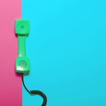 phone cord: Retro green telephone tube on striped blue and pink background - Minimal design Stock Photo