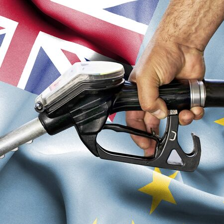 Gasoline consumption concept - Hand holding hose against flag of Fiji