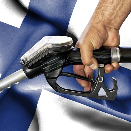 Gasoline consumption concept - Hand holding hose against flag of Finland